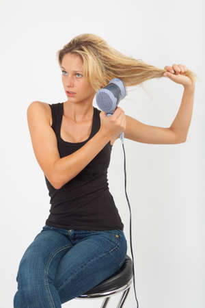 blow dry: Young blonde blow dries her hair on the side