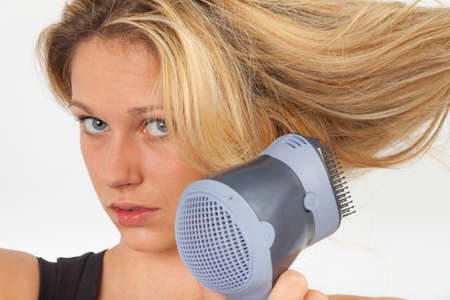 blow dry: Young blonde blow dries her hair on the side and looking at the camera