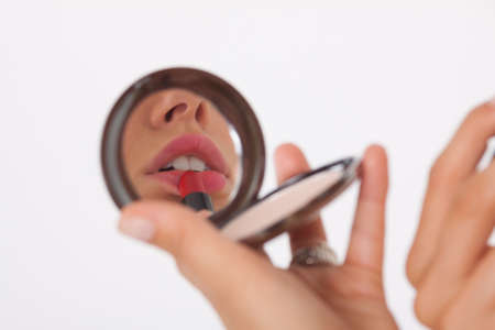 putting lipstick: Young woman in makeup mirror, putting on lipstick Stock Photo