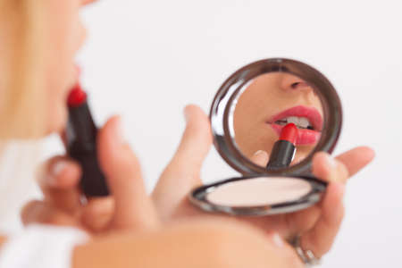 putting lipstick: Young woman putting on lipstick looking in make-up mirror