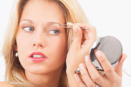 pinzas: Joven mujer depilarse las cejas con pinzas Foto de archivo