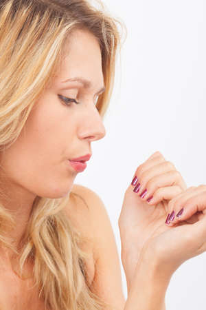 beautify: Young woman blowing on her fingernails for drying nail polish