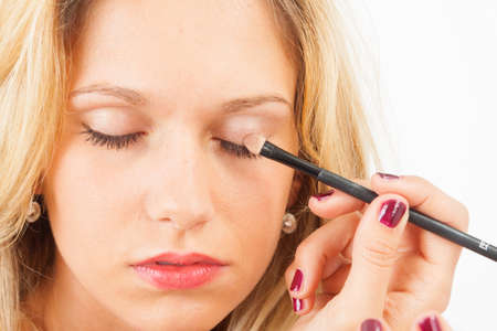 embellished: Young woman putting on eyeshadow with closed eyes