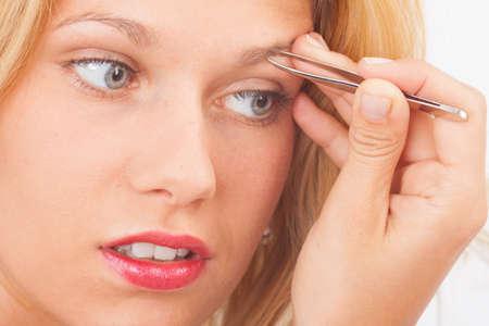 tweezers: Joven mujer depilarse las cejas con pinzas Foto de archivo