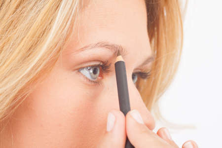 beautify: Young woman extends her eyebrows with the stylus