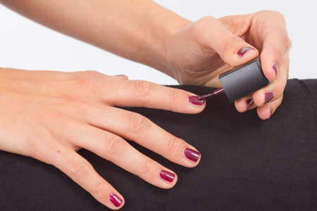 beautify: The hands of a young woman applying nail polish
