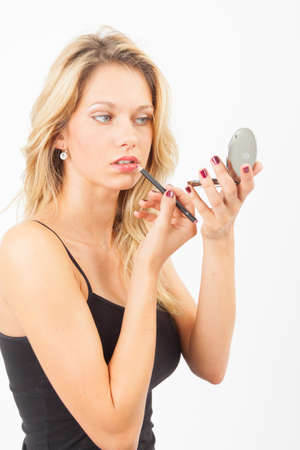 embellished: Young woman lines up her lips with a pen Stock Photo