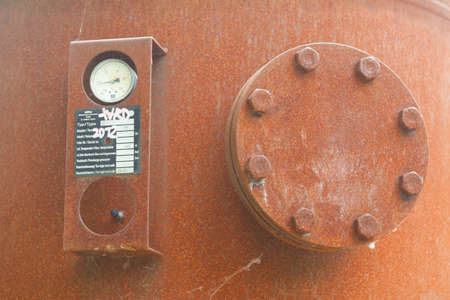 compressed air: Rusted container with screw flange and pressure gauge Stock Photo