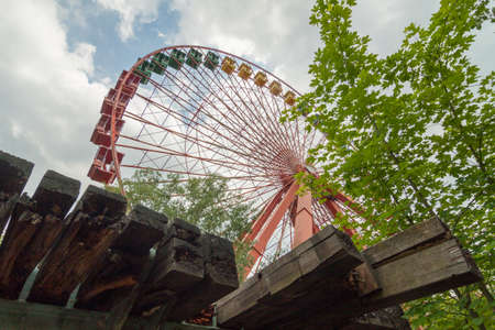 wooden beams: Abandoned ferris wheel with wooden beams in the foreground