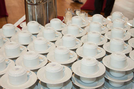 saucers: Stacked cups and saucers on a buffet