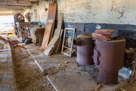 pigsty: Rusty heater parts in an abandoned pigsty on Langeland, Denmark Stock Photo