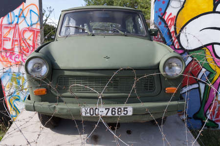 Green painted Trabant trapped in the wall and protected with barbed wire