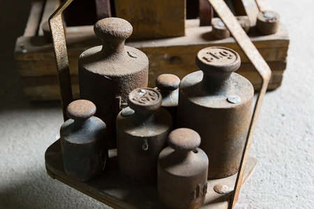 kilograms: Old, rusty weights on a weighing scale