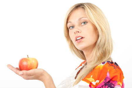 demanding: Young woman presenting an apple and looking demanding at the camera Stock Photo