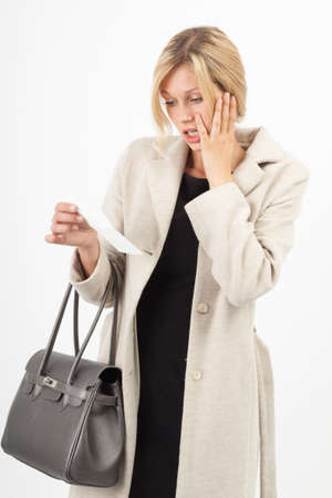 dismay: Young woman looking shocked at an invoice Stock Photo