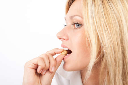 nibbling: Young woman nibbling on a peanut