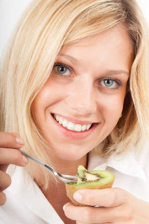 Young woman spooning a fresh kiwi