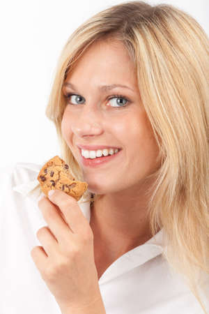 snacking: Young woman eating a chocolate chip cookie