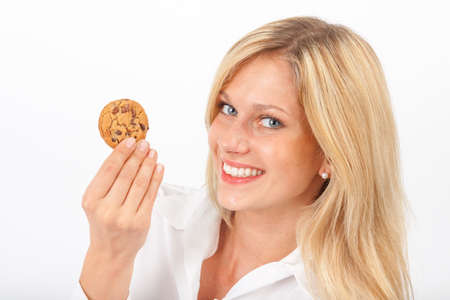 nibble: Young woman eating a chocolate chip cookie