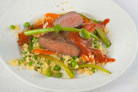 carnes y verduras: Cordero asado con arroz, guisantes y albahaca Foto de archivo
