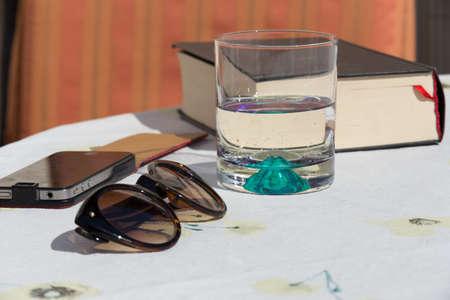 vasos de agua: Naturaleza muerta con vasos, vidrio, libro y Smartphone Foto de archivo
