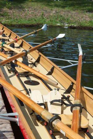 bateau de course: Rennruderboot mit Rudern an einem Steg