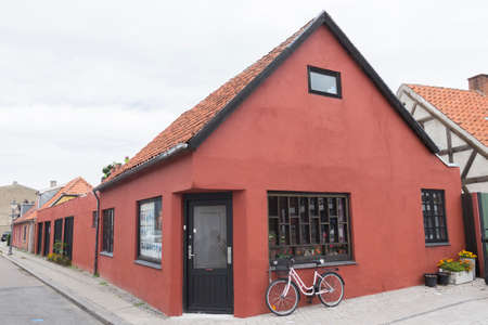 corner of house: Red Corner House in Nykobing with a small shop and a bike in front