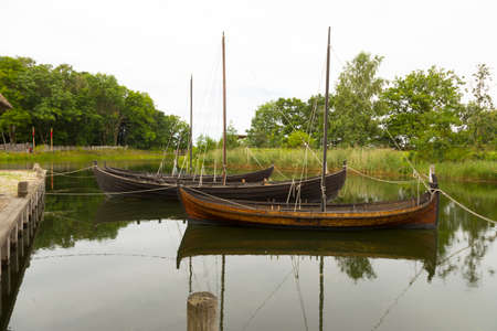 precisely: Three historic sailboats at the wharf on a lake Stock Photo