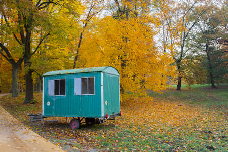 discolored: Green Blue Construction trailer in a Park in front of autumnal discolored forest