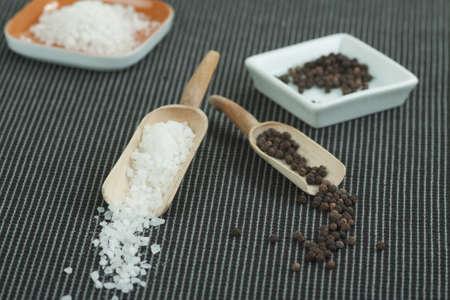 holz: Pfefferkörner und grobes Salz in hölzernen Scheffeln Stock Photo