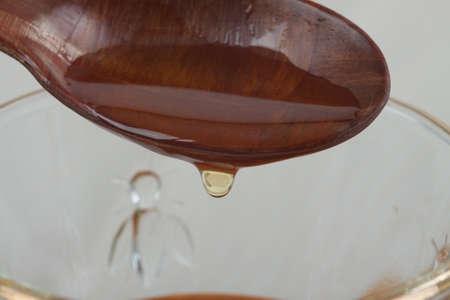 glas: Honig tropft von einem Holzlöffel in ein Glas mit Bienenmuster Stock Photo