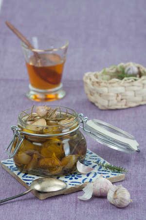 Hintergrund: Eingelegter Knoblauch im Weckglas mit einem Honigglas im Hintergrund