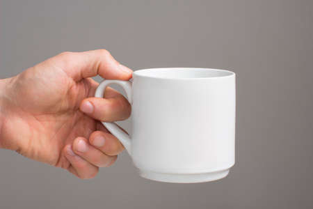left hand: Hand holding white cup Stock Photo