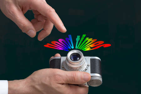 good times: Close view of a vintage camera in mans hands and text GOOD TIMES in a dark background. Stock Photo