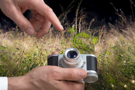 Close view of a vintage camera in mans hands in a  meadows background. photo
