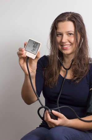 own blood: A young woman monitoring her own blood pressure