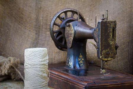 De scène met een oude naaimachine en witte draad. Stockfoto