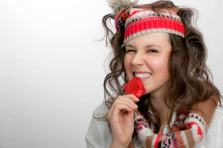 red condom: Portrait of girl with knitted hat,  scarf and tousled hair  holding with teeth a red condom pack Stock Photo