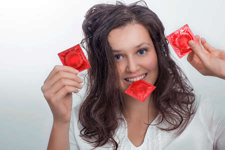 Smiling girl with  with three red condom packs