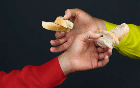 eating right: Two mens hands with two peaces of a white bread in a dark background
