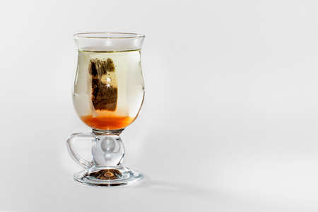 Close view of a glass of  tea with a teabag in a white background Stock Photo