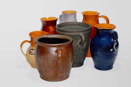 ollas de barro: Siete vasijas de arcilla en un fondo blanco
