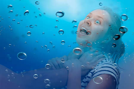 Young woman being strangled under the water with bubbles around