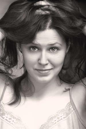 zerzaust: Portrait einer jungen Frau mit zerzausten Haaren in schwarz wei� Lizenzfreie Bilder