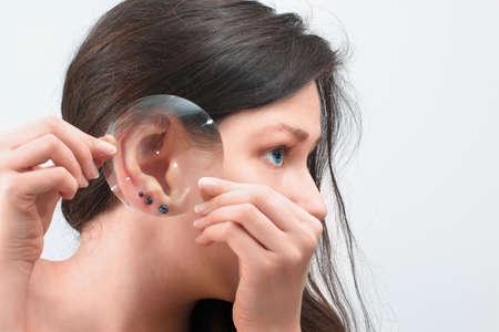 Womans oor met drie oorbellen door het vergrootglas op een witte achtergrond