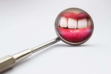 Tandarts spiegel met reflectie van de tanden in een witte achtergrond