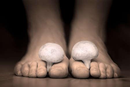Sluit het oog op een witte champignons tussen de tenen voeten imiteren tenen schimmel