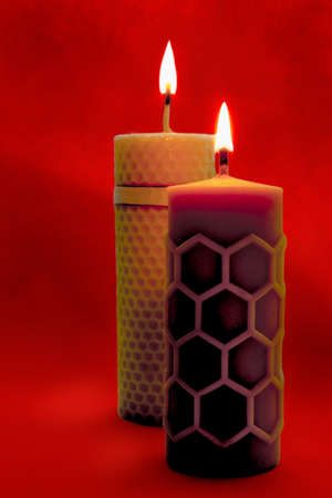 beeswax: Close view of two beeswax candles flame on a red background