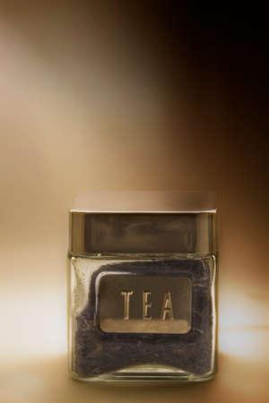 fondo degradado: Tarro vidrioso con la etiqueta y el t� en un fondo degradado Foto de archivo