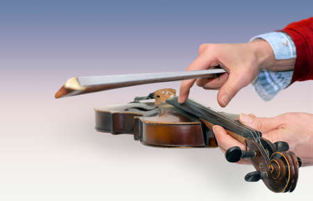 Mans hands holding an old violin and a bow in a color gradient background photo